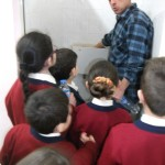 The handyman showed the children how to place the bottles in the cisterns.